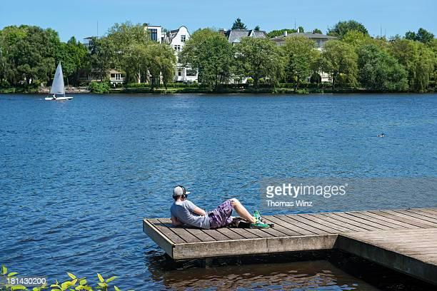 Man relaxing along Aussenalster lake