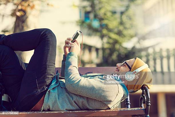 man relaxing and luying on a bench after work
