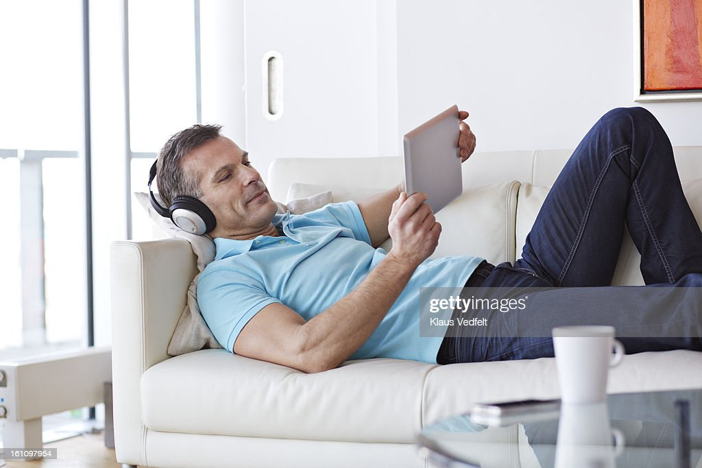 Man relaxing at couch w. tablet & headphones : Stock Photo
