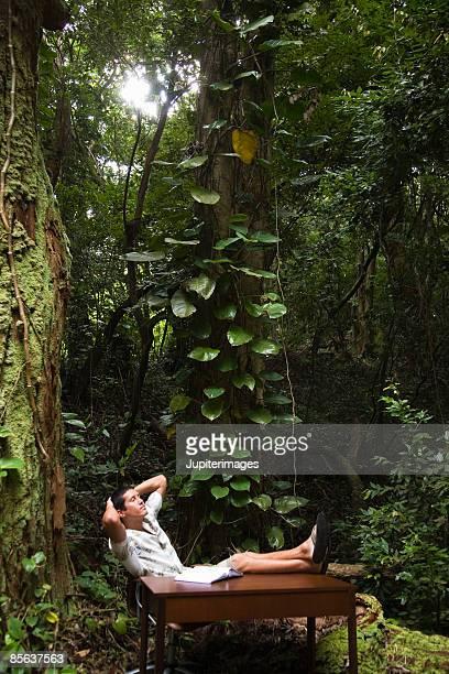Man relaxing at desk in rainforest
