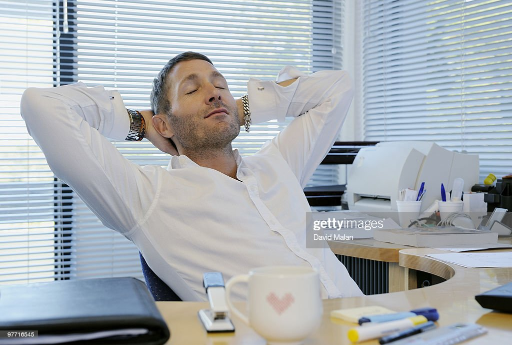 Man relaxing at his desk in office environment : Stock Photo