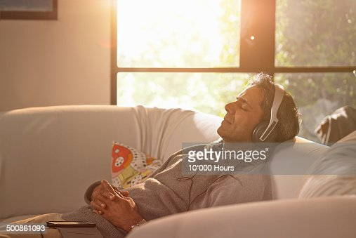 A man relaxing at home listening to music.