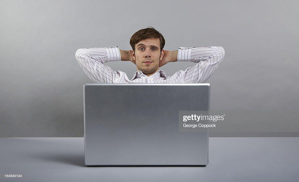 Man relaxing behind laptop : Stock Photo