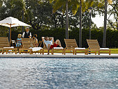 Man relaxing by hotel pool and waiter serving two women in background