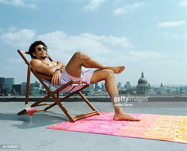 Man Relaxing in a Deck Chair on a Roof Against a London Skyline