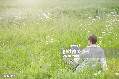 Man relaxing in a summer meadow with a tablet : Stock Photo