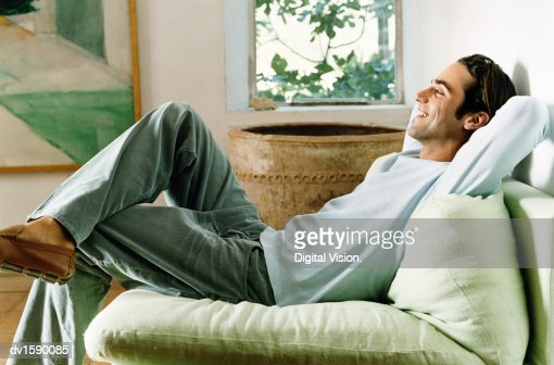 Man Relaxing in an Armchair in a Living Room with His Hands Behind His Head : Stock Photo