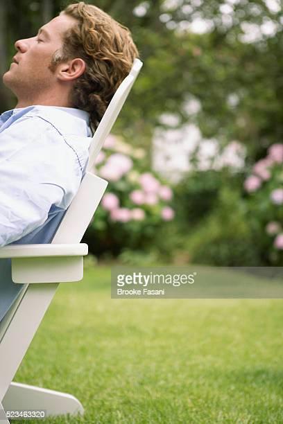 Man relaxing in backyard