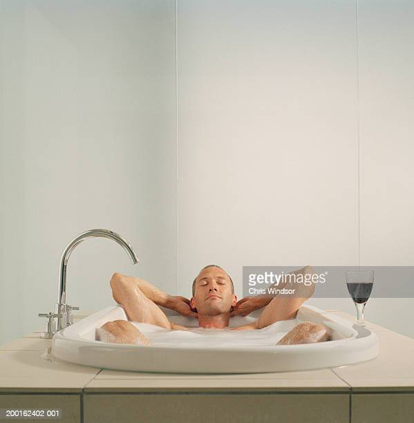 Man relaxing in bath with glass of red wine, eyes closed