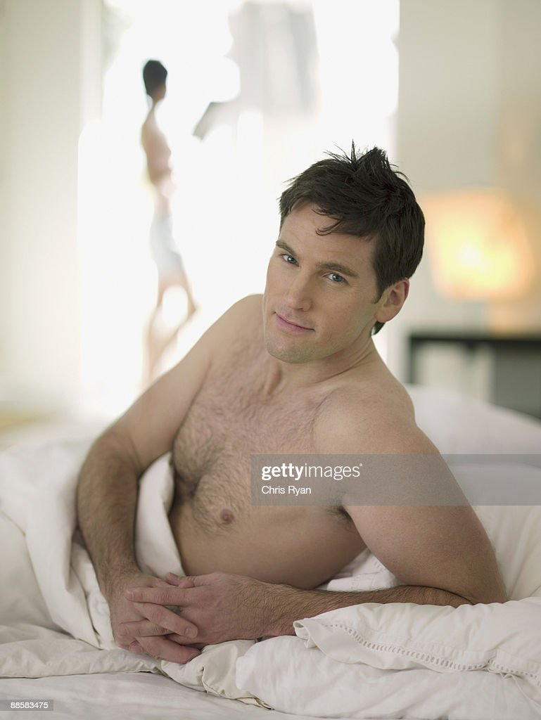Man relaxing in bed : Stock Photo