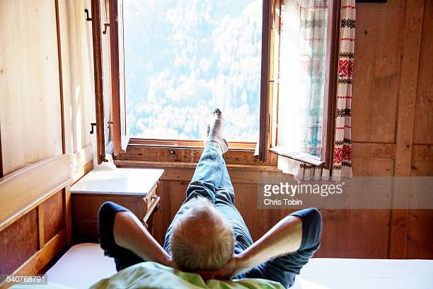Man relaxing in cabin with feet out the window