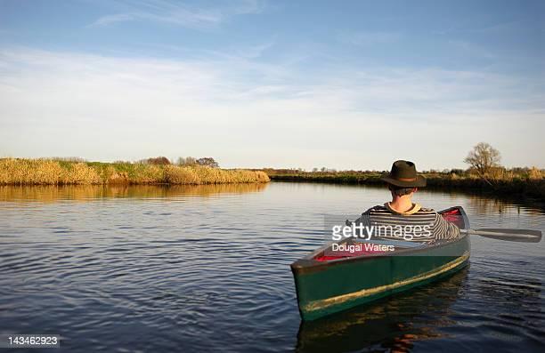 Man relaxing in canoe on river.