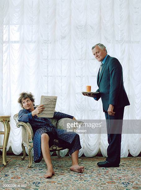 Man relaxing in chair being served drink by mature man