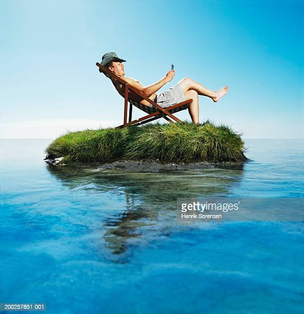 Man relaxing in deckchair on grass island using mobile phone