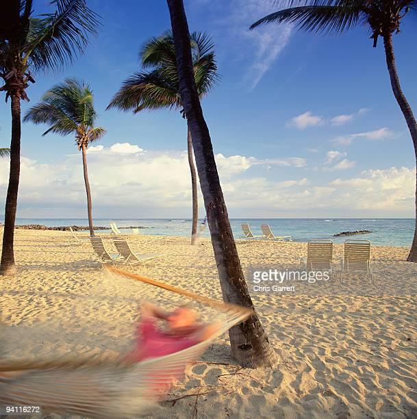 Man relaxing in hammock on tropical beach