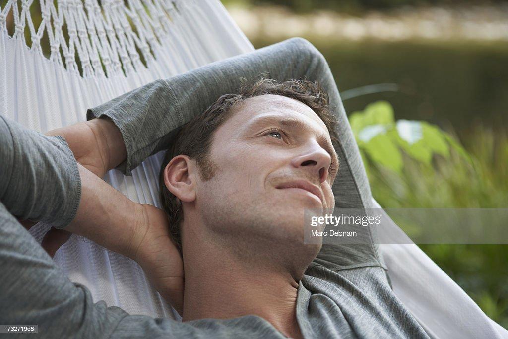 Man relaxing in hammock, outdoors : Stock Photo