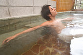 Man relaxing in hot tub, side view, Japan