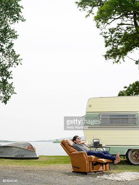 man relaxing in recliner next to lake
