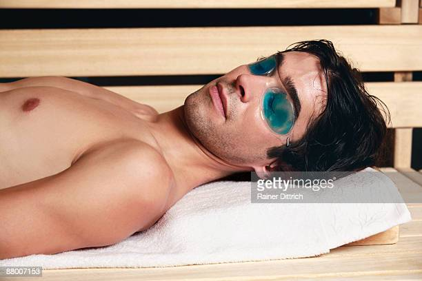 Man relaxing in sauna, eyes closed