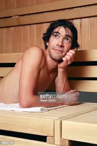 Man relaxing in sauna, smiling