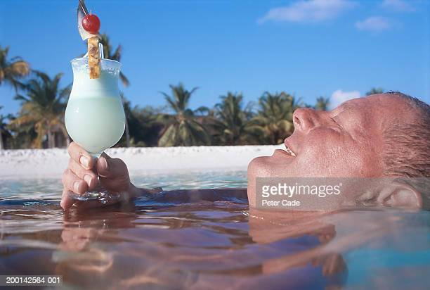 Man relaxing in sea holding tropical drink, smiling, side view