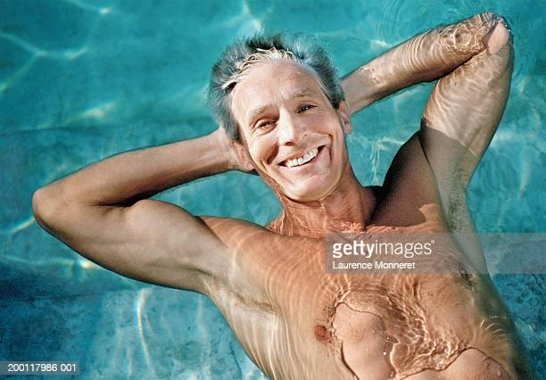 Man relaxing in swimming pool, hands behind head, portrait