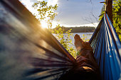 Man relaxing in the hammock. View on lake and sunrise