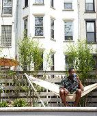 Man relaxing in urban backyard hammock
