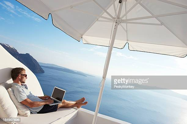 Man Relaxing Luxury Balcony with Laptop Mediterranean Island View