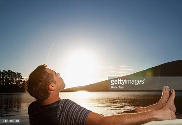 Man relaxing near lake at sunset