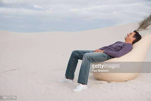 A man relaxing on a beanbag chair outdoors