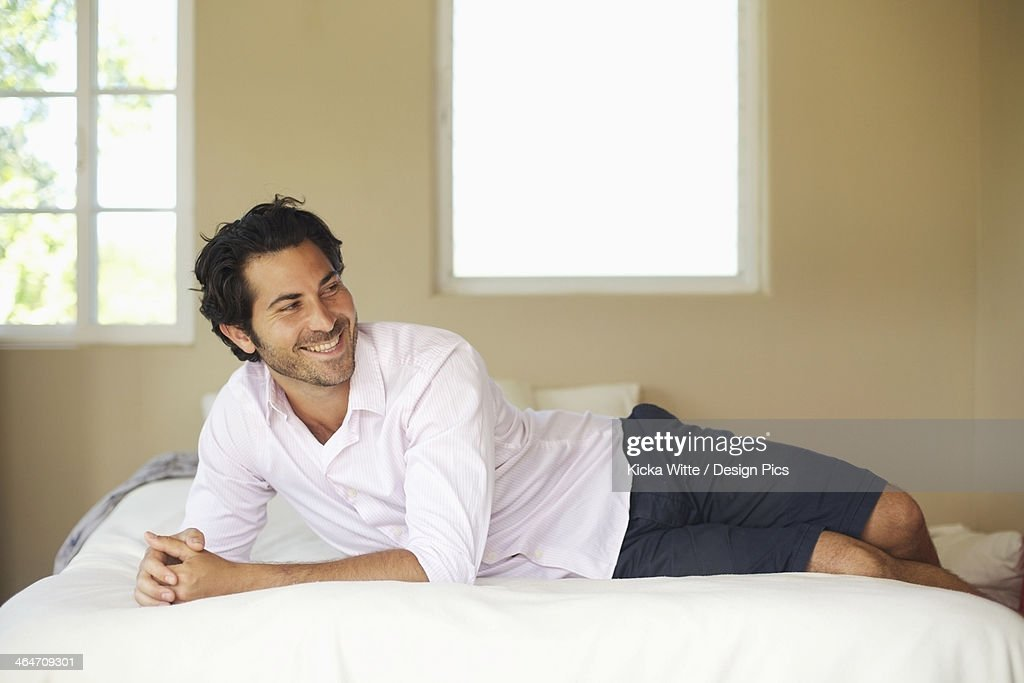 A Man Relaxing On A Bed And Smiling