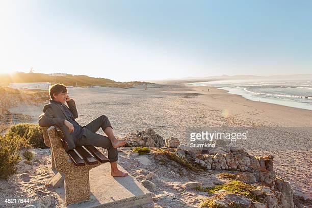 Man relaxing on beach bench