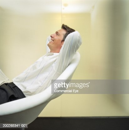 Man relaxing on chair, arms behind head, side view : Stockfoto