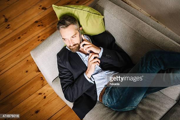 Uomo rilassante sul divano e utilizzando il telefono cellulare