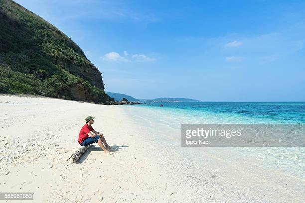Man relaxing on deserted tropical island beach