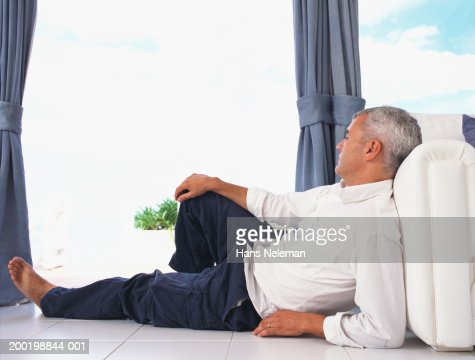 Man relaxing on floor, looking out window, side view : Stock Photo