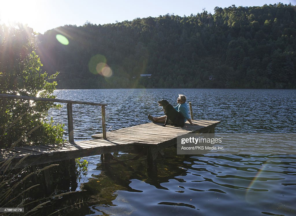 Man relaxing on lake pier with dog, sunrise