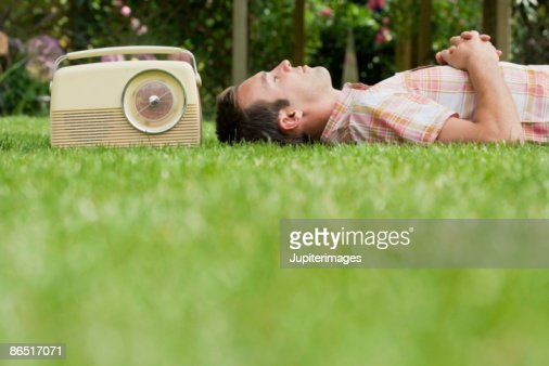 Man relaxing on lawn with old-fashioned radio : Foto stock