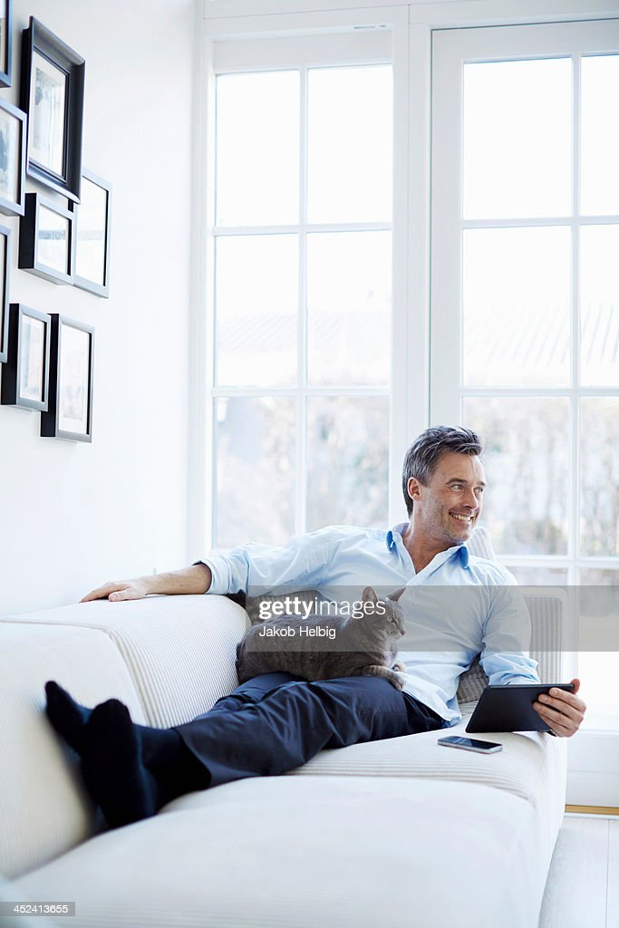 Man relaxing on sofa using digital tablet with cat : Stock Photo