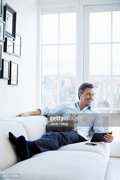 Man relaxing on sofa using digital tablet with cat