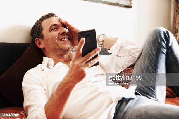 Man relaxing on sofa using  smartphone
