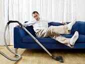 Man relaxing on sofa, vacuum cleaner working by itself beside (digital composite)