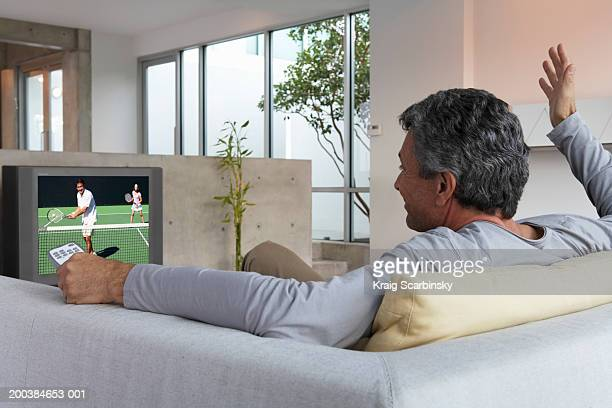 Man relaxing on sofa watching tennis on television,gesturing with hand