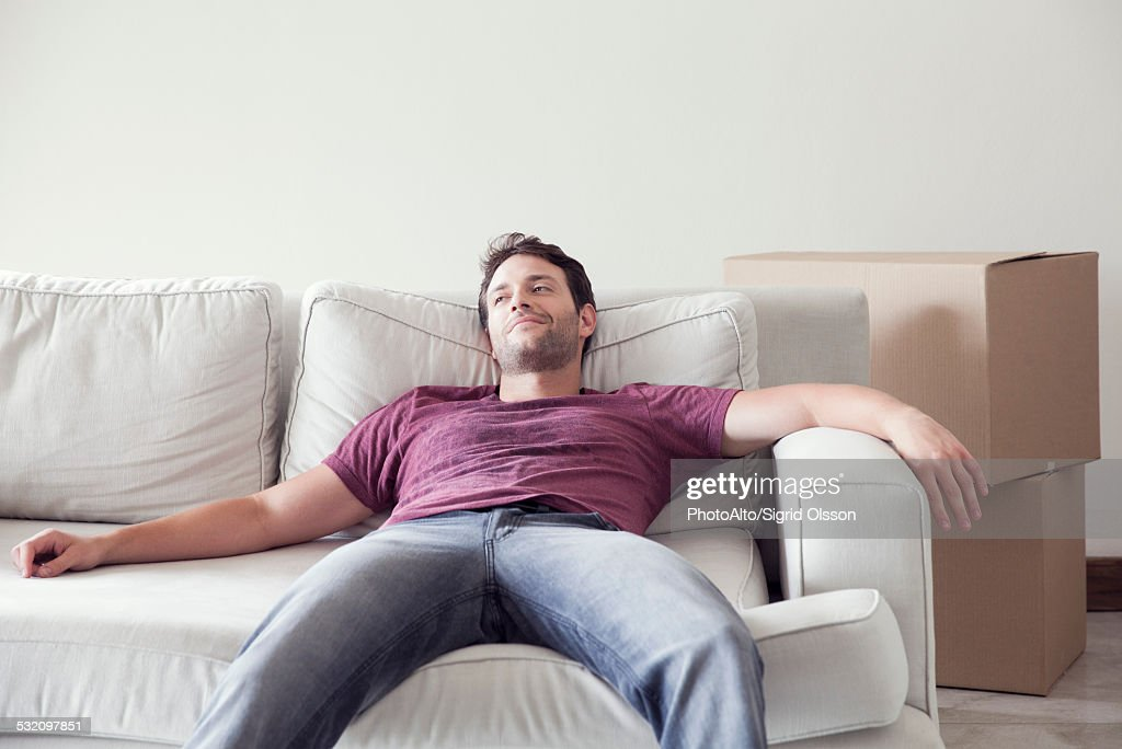 Man relaxing on sofa while moving house