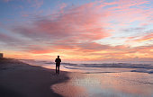 Man walking on the beautiful  beach at sunrise. Atlantic Beach, North Carolina.