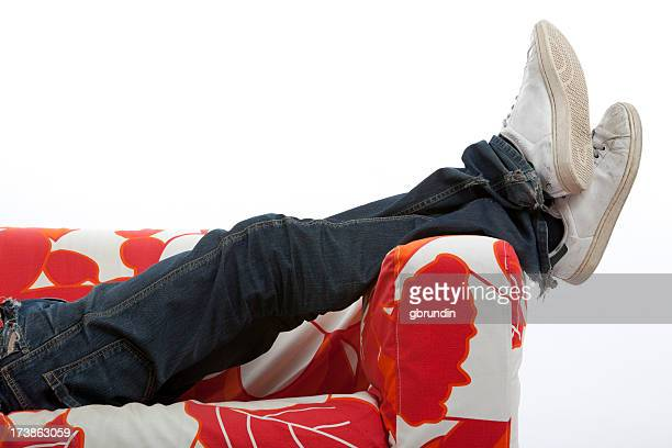 A man relaxing on the sofa wearing white sneakers and jeans