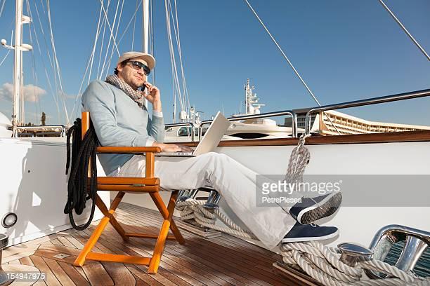 Uomo d'affari su yacht rilassarsi e leggere le e-mail