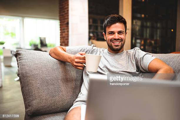 man relaxing online on sofa