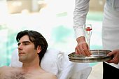 Man relaxing poolside and servant with champagne glass
